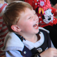 boy laughing at a kids magic show