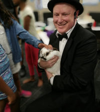 Children petting a magic rabbit held by kids entertainer and magician Jimmy Marvel