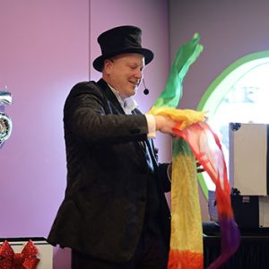 Jimmy Marvel pulls a rainbow streamer from an empty rolled up poster